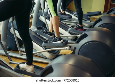 Closeup shot of legs of a female using elliptical trainer in a gym