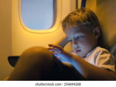 Close-up shot of a little boy playing on touch pad during in the plane. Child looking tired or bored