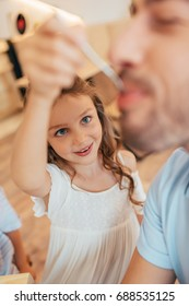 close-up shot of little girl feeding her father
