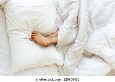 Closeup shot of little girl sleeping upside down and holding feet on pillow