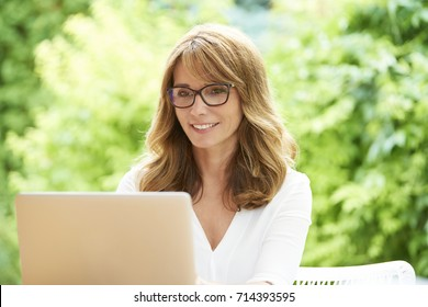 Close-up shot of a lovely attractive middle aged woman using laptop while sitting at home in the garden and relaxing.