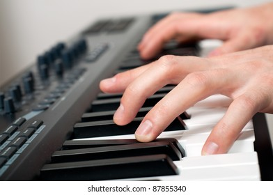 closeup shot of male hands playing the piano in the studio