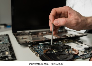 Closeup shot of male hands working on disassembling and cleaning circuit board in laptop using brush