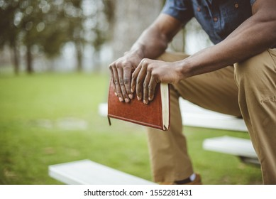 A closeup shot of a male holding the bible while sitting on a park table with a blurred background