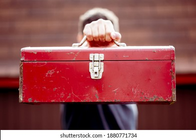 A closeup shot of a male holding a toolbox in front of his fa