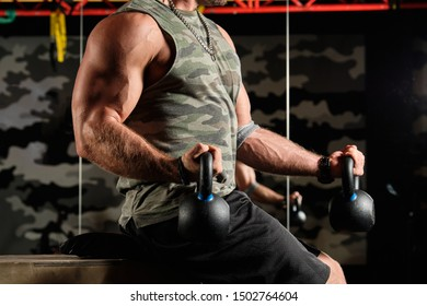 Close-up shot of male inflated torso and muscular arms with kettlebells in the gym