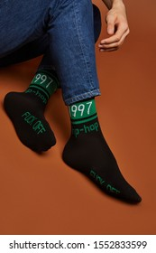 """Close-up shot of male legs in blue jeans and black socks with green stripes and lettering """"1997, hip-hop, fuck off"""". The photo is made on the brown background."""