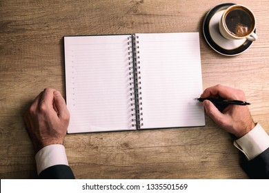 Closeup shot of a man taking down note in a personal organizer. Businessman is writing in a diary in his office. Blank page to write it on your own message