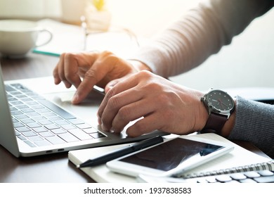 Close-up shot of man's hand with watch on his wrist. using keyboard of laptop computer on office desk. businessman working in office. Business investment-finance accounting concept.