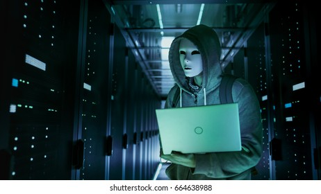 Close-up Shot of a Masked Hacker in a Hoodie Standing in the Middle of Data Center full of Rack Servers and Hacking it with His Laptop.