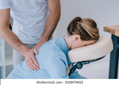 close-up shot of masseur massaging back of female client