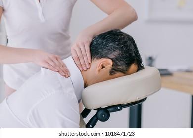 close-up shot of masseuse doing neck massage for businessman