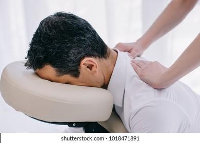 close-up shot of masseuse doing seated back massage for businessman