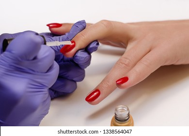 Closeup shot of master in rubber gloves сovering red nails with top coat in the beauty salon. Perfect nails manicure process
