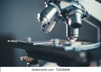 Close-up shot of microscope with metal lens at laboratory.