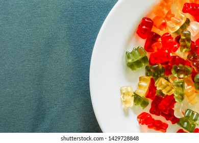 Close-up shot of mixed color gummy bears placed on a white plate with copy space – Sugary soft treats with fruit flavor – Funny shape chewie candies