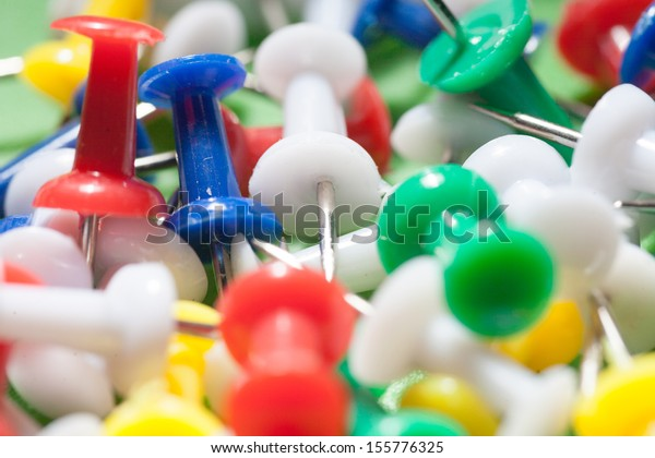 closeup shot of mixed colors office push-pins, may be used as background, angle view