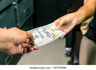 Closeup shot of money passing between two businessmen hands corruption under table. Receiving illegal payoff. American dollars cash. We have deal, but keep it quiet.