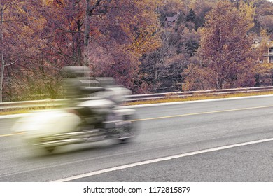Closeup shot of a motorcycle in motion during fall season
