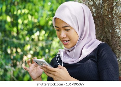 Close-up shot of muslim lady in hijab using smartphone with earphone. Malaysian young woman or student looking at smartphone.