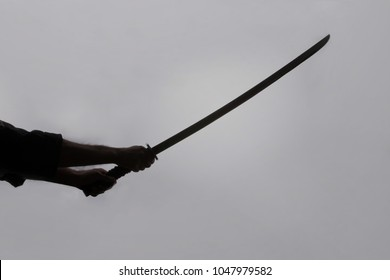A close-up shot of a ninja man's hand holding a sword and raising it.