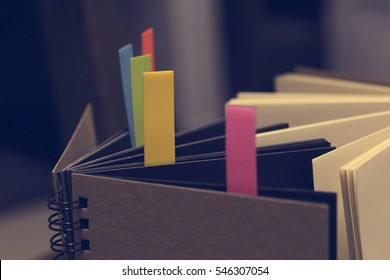 Closeup shot of notebook with color note tab. Notebook with colors note tab on wooden table background, Vintage picture tone.