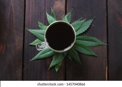 A closeup shot o cannabis, hemp, CBD or THC infused black coffee on dark wood background