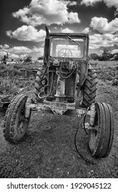 Closeup shot of old half disassembled tractor in the village or Farm Country. Agricultural machinery. Vintage industrial era. Black and white photography