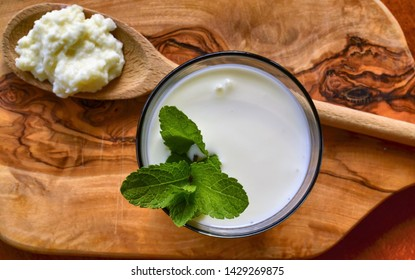Close-up shot on a full glass of white Kefir enriched with some mint leaves. On the cutting board a wooden spoon full of Kefir ferments.