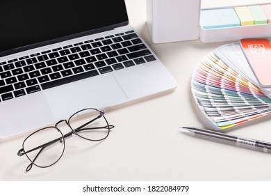 A closeup shot of an open laptop, glasses, a notepad, pen, and a fan ral