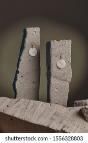 Close-up shot of a pair of earrings fixed on the gray half-sawn stones on the sage green background. Each earring is made as a golden hook with dangling nacre disc.