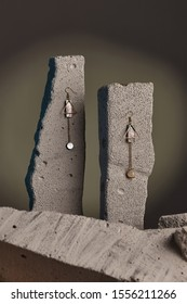 Close-up shot of a pair of earrings with golden geometric-shaped pendants, dark nacre plates, gems and chains. The earrings are fixed on the gray half-sawn stones on the sage green background.