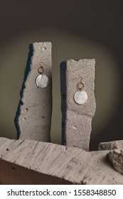 Close-up shot of a pair of hook earrings fixed on the gray half-sawn stones on the sage green background. Each of the earrings is decorated with a golden wavy ring and a round nacre disc.