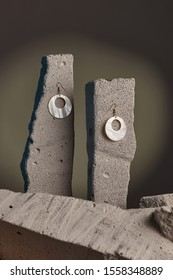 Close-up shot of a pair of hook earrings fixed on the gray half-sawn stones on the sage green background. The golden earrings are decorated with holed nacre discs.