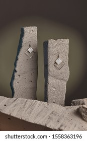 Close-up shot of a pair of hook earrings fixed on the gray half-sawn stones on the sage green background. Each of the earrings is decorated with two diamond-shaped silver and nacre pendants.