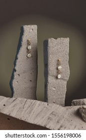 Close-up shot of a pair of stud earrings fixed on the gray half-sawn stones on the sage green background. Each golden earring is made as a string of golden wire balls and nacre gem pellets.