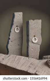 Close-up shot of a pair of stud earrings fixed on the gray half-sawn stones on the sage green background. Each earring is made as a golden semi-sphere with dangling holed nacre disc.