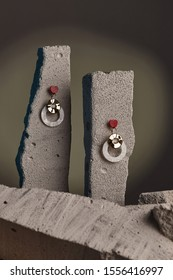 Close-up shot of a pair of stud earrings fixed on the gray half-sawn stones. Each earring is made as a red gem heart-shaped base with dangling wavy golden disk and a white nacre holed circle.