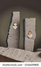 Close-up shot of a pair of stud earrings fixed on the gray half-sawn stones on the sage green background. Each golden earring is made as golden and nacre rhombus-shaped plates.