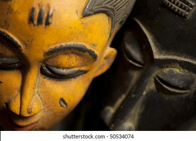 Close-up shot of a pair of wooden African tribal masks with color contrast. Macro lens was used with a shallow depth of field on the black mask to create a sense of mystery.