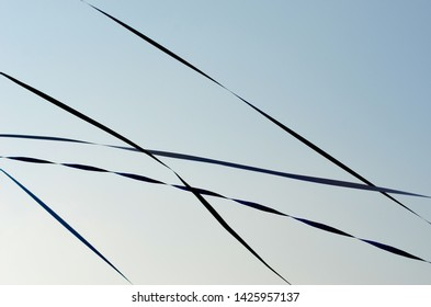 A close-up shot of paper streamers which have been thrown from a boat to the dock. They are dark blue, but appear almost black against a blue sky.