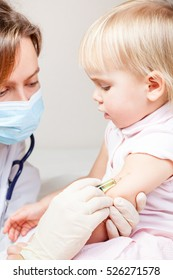 Close-up shot of pediatrician giving an intramuscular injection of a vaccine to a little girl