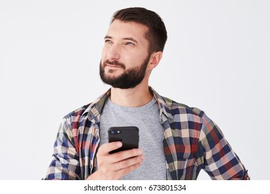 Close-up shot of pensive bearded man looking upward while texting on telephone isolated over white background