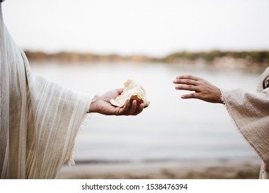A closeup shot of a person wearing a biblical robe giving bread to another person with a blurred background