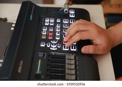 A close-up shot of a person's hand operating a set of image control devices. Live stream work.