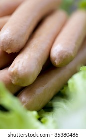 Close-up shot of a pile of fresh sausages on some lettuce