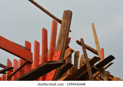 A close-up shot of the planks and frame of an unfinished boat. Some have been painted red. The sky is overcast.