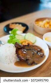 Close-up shot of a plate of pork chops with mushroom sauce over some warm white rice