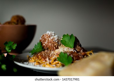 A close-up shot of a plate of rustic spaghetti and meatballs with a bowl of meatballs, parmesean cheese, and fresh parsley.