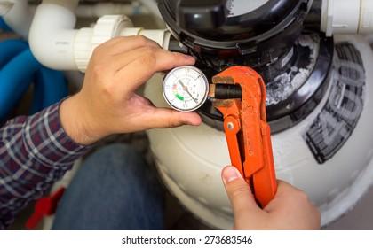 Closeup shot of plumber installing manometer on pipe